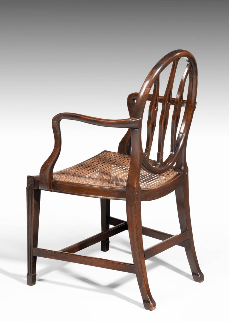 A George III period mahogany framed elbow chair. Of quite delicate form with well executed carved decoration. Square tapering legs with blocked feet.
