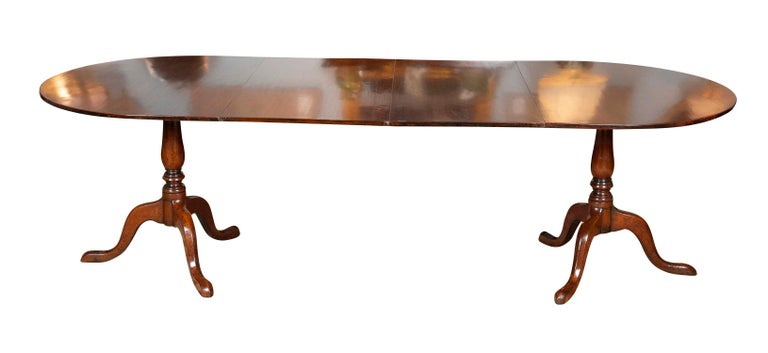 George III period mahogany twin pedestal dining table having 'D' shaped ends with 2 leaves on turned column tripod bases. Previously sold by renowned London based antiques dealer Norman Adams and retaining original label to the underside, circa