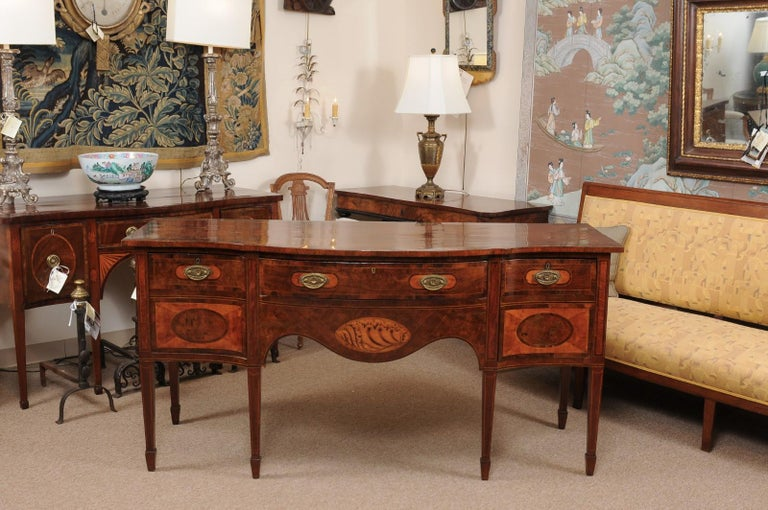 An English George III serpentine mahogany and satinwood sideboard featuring 2 cellarette drawers, center silver drawer and shaped apron below with shell inlay ending on tapered legs with spade feet.