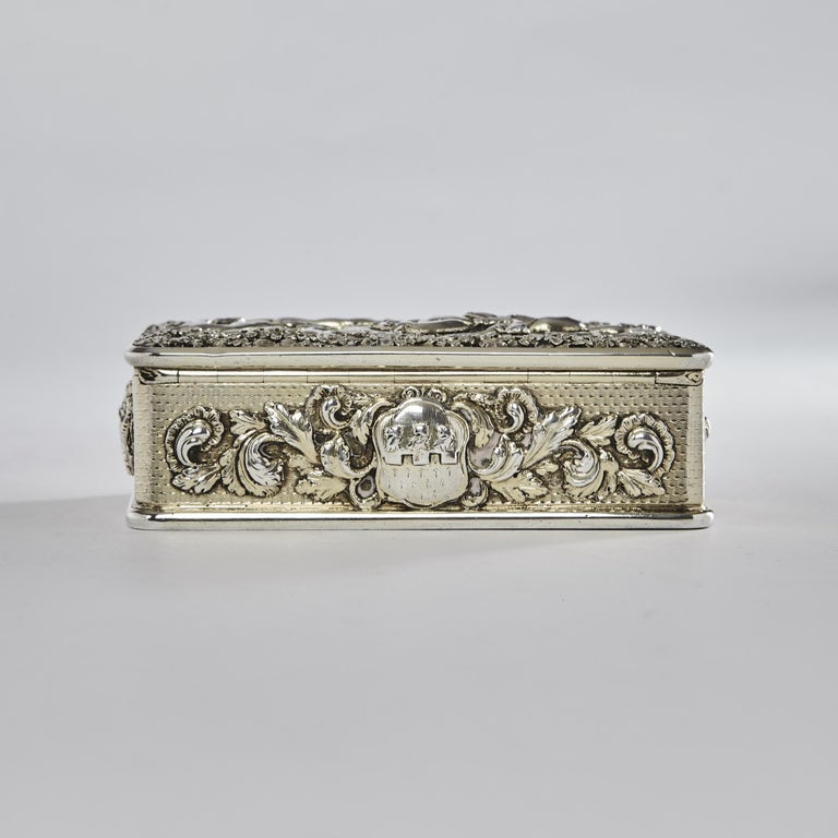 Fine Georgian snuff box with cast scene on the lid of huntsmen and hounds chasing a fox through the woods. The sides of the box have cast and applied foliate cartouches incorporating crests and arms for Williams of Dorset. This exceptionally heavy