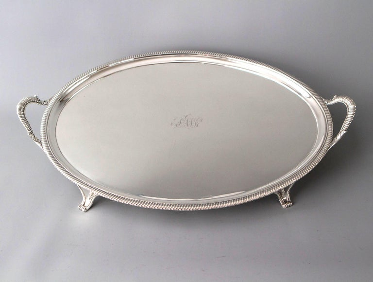 A very good quality George III oval silver tray with twin handles and gadrooned edges. The whole standing on four scrolled panel feet.   Clearly marked to the underside for London 1811 by Peter and William Bateman.   This is an exceptionally