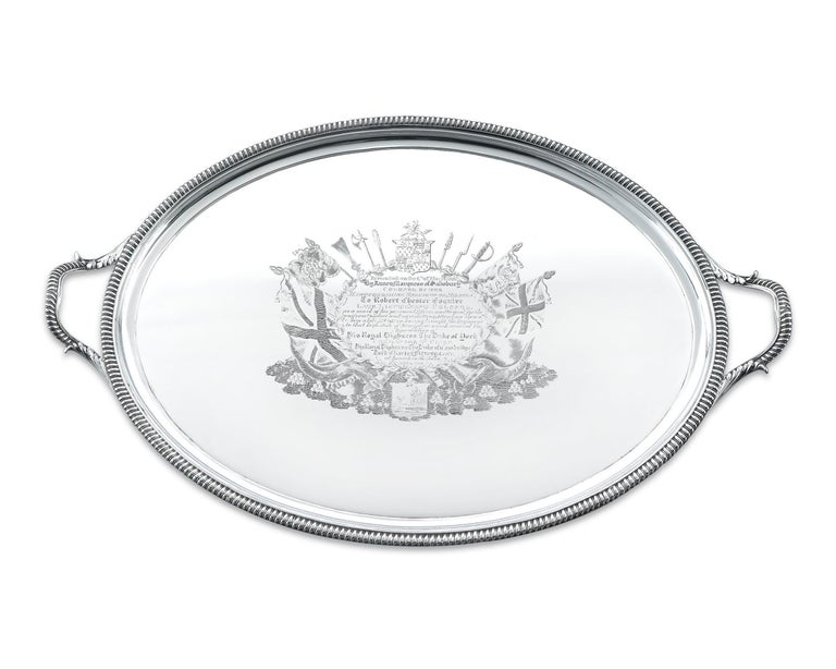 This fascinating George III silver tray is a work of skillful English artistry, intricately chased and engraved it represents a prestigious commemorative gift for service. The tray rests on 4 bracket feet with oval handles and a delightful gadrooned