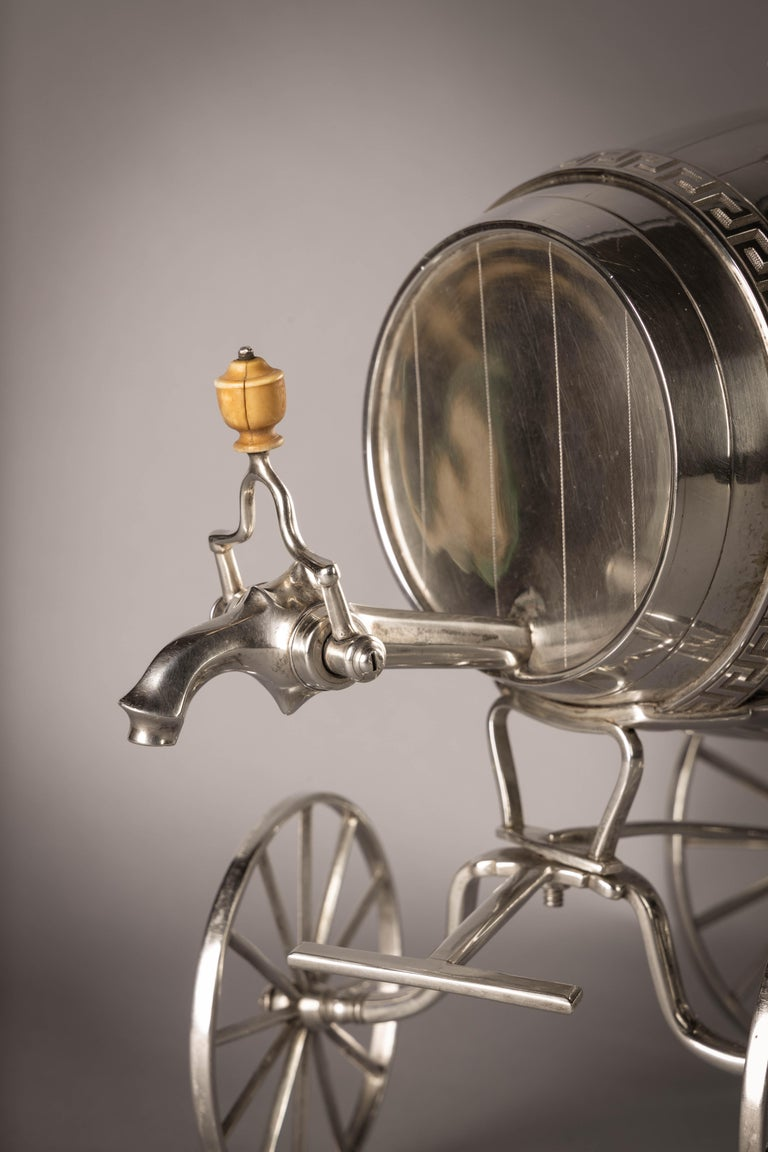 Modelled as a wine barrel on wheels with a detachable putti finial. Marked: London, 1807, Maker: William Burwash.