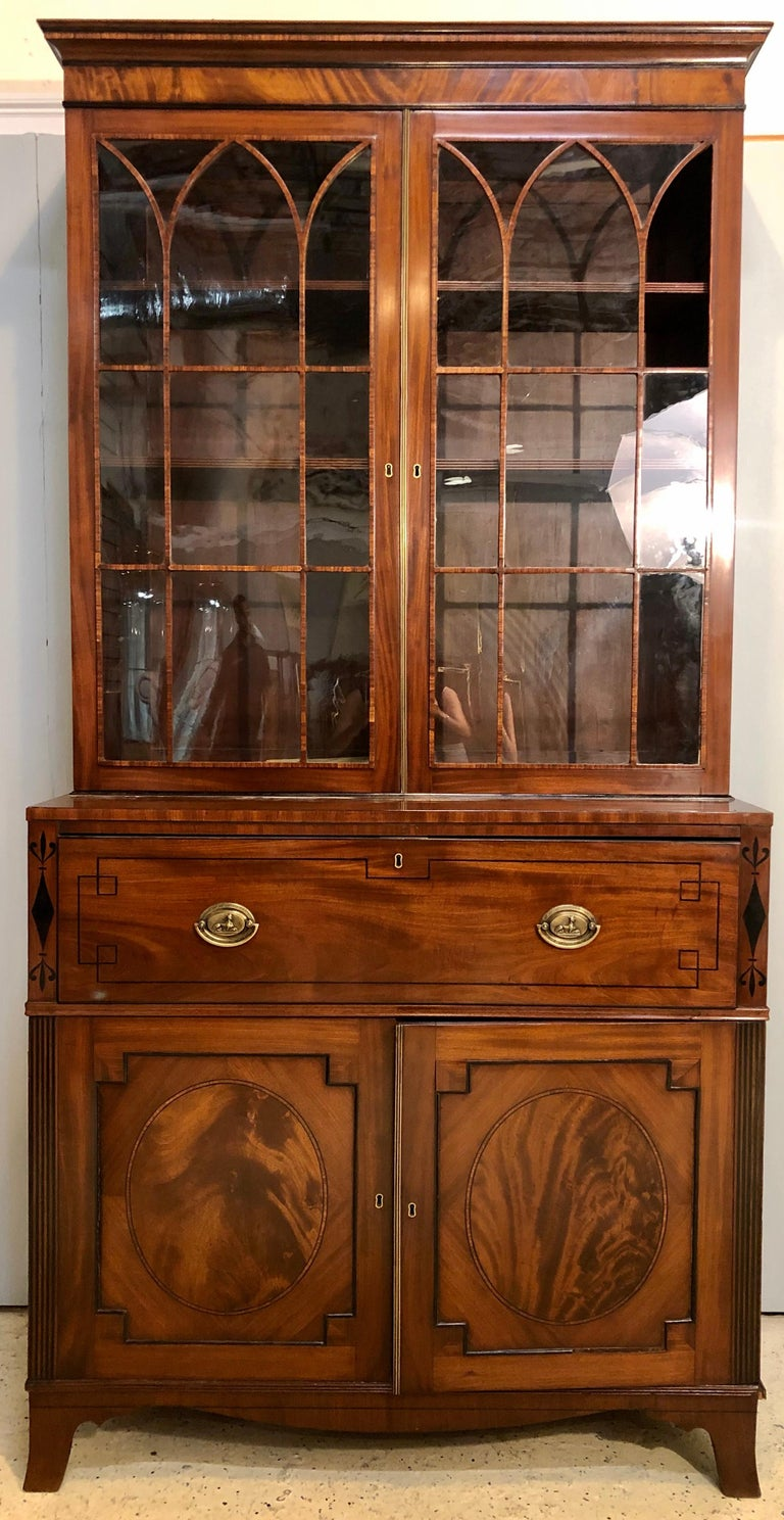 George III style mahogany secretaire bookcase, circa 1860. Flame mahogany with ebony inlays. The rectangular detailed cornice above a pair of glazed doors with fretwork mullions, the lower section with a secretary drawer faced as a single drop down