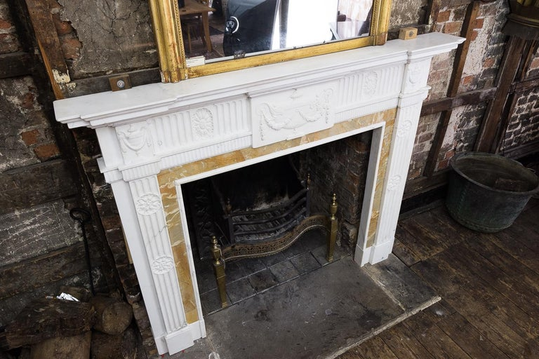 A George III style statuary and sienna marble neoclassical chimneypiece, possibly Irish, early 20th century, the inverse breakfront moulded shelf above tablet with classical tazza carved in relief flanked by fluted frieze centred by oval paterae,