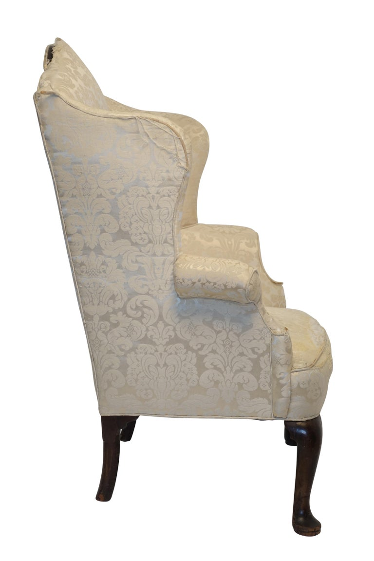 Wonderfully shaped Georgian wingback armchair with shapely wings and arch top backrest with swooping arms, standing on a pair of Queen Anne legs with pad feet on the front and very typical round Georgian back legs. England, circa 1800. Will need