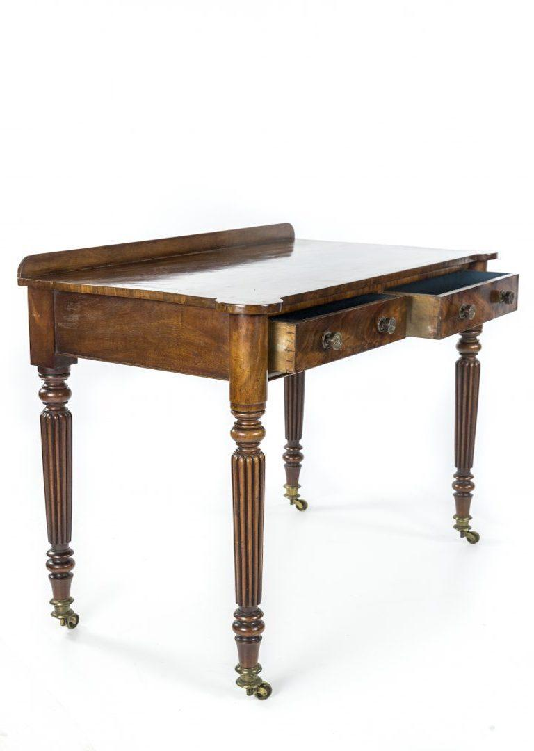 A George IV figured mahogany side or writing table attributed to Gillows, the cross banded top over two drawers on turned and reeeded tapering legs to brass caps and castors  Gillows of Lancaster and London, also known as Gillow & Co., was an