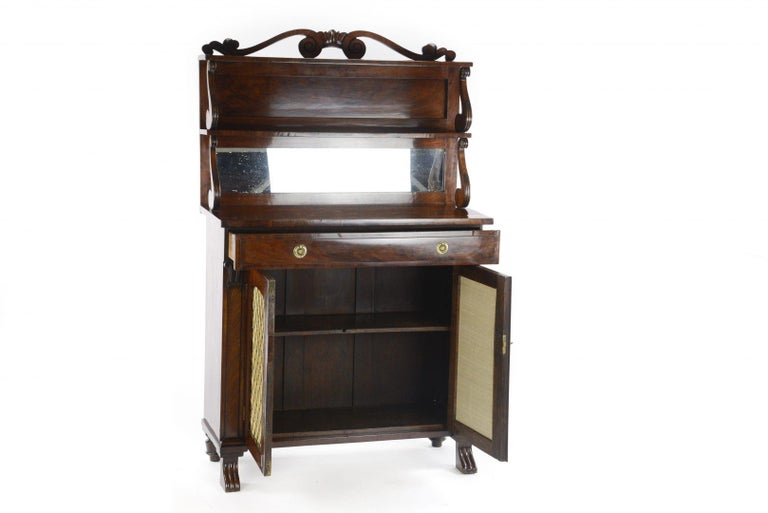 A modest George IV mahogany chiffonier dating to circa 1825, having an upper section with two mahogany shelves with a gallery supported on finely carved brackets, two rectangular mahogany doors with brass grilles and silk lined panels and having