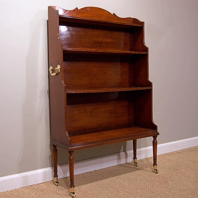 George IV mahogany library bookcase with brass castors.