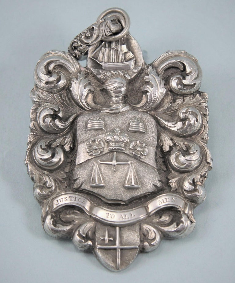 Interesting George IV silver sea-coal meter badge. Unmarked. Maker's mark AD stamped on the ring attachment. England, circa 1824.   The badge is of shaped form with foliate scroll decoration and an armorial with motto beneath in the centre. The