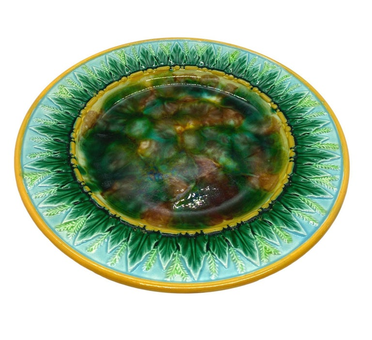George Jones Majolica 9-in plate with mottled center, green wheat leaves and wheat stalks on turquoise, the inner and outer border glazed in yellow/ochre. The reverse with impressed 'GJ' monogram and painted pattern number '1808,' English, circa