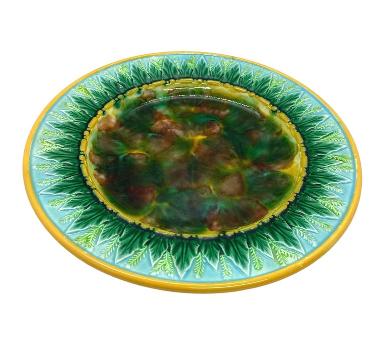George Jones Majolica 9-in plate with mottled center, green wheat leaves and wheat stalks on turquoise, the inner and outer border glazed in yellow or ochre. The reverse with impressed 'GJ' monogram and painted pattern number '1808,' English, circa