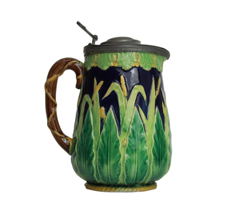 George Jones Majolica Cobalt blue wheat pitcher with pewter lid, English circa 1873, the body molded with acanthus leaves glazed in varying shades of green, with naturalistically glazed green and yellow wheat sheaves, with yellow glazed roping to