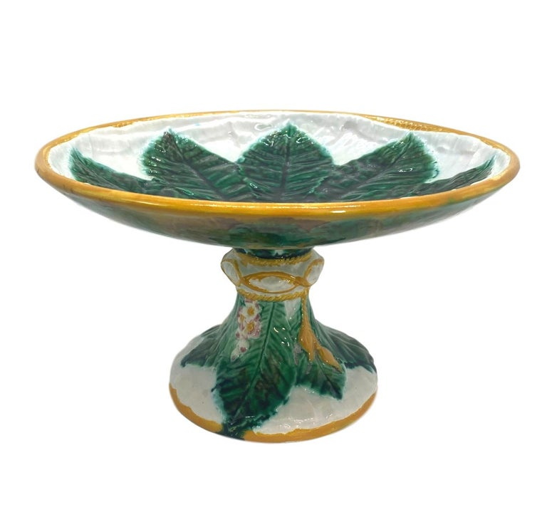 George Jones Majolica elevated comport, with a central green glazed horse chestnut leaf on a relief- molded white napkin, the border glazed in ochre, the pedestal wrapped with an ochre tassel, with horse chestnut leaves and blossoms, English, circa