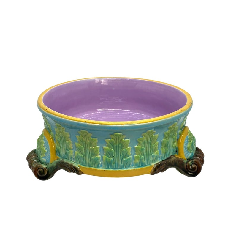 George Jones Majolica dog bowl, with green glazed acanthus leaves on a turquoise ground, bordered in ochre, with applied bowed cartouches above each of the scrolled feet, the interior glazed in pink, the reverse with impressed 'J' for 1884 and