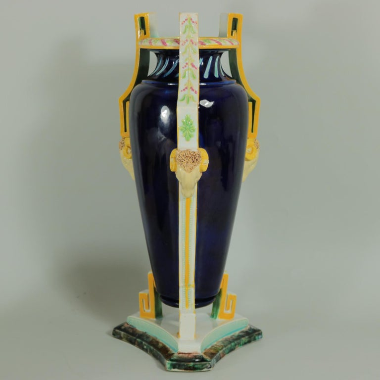 George Jones Majolica vase which features ram heads supporting the elaborate handles. Berry decoration to the handles. Colouration: cobalt blue, white, yellow, are predominant. Bears a pattern number, 'W'. Book reference ,'George Jones Ceramics
