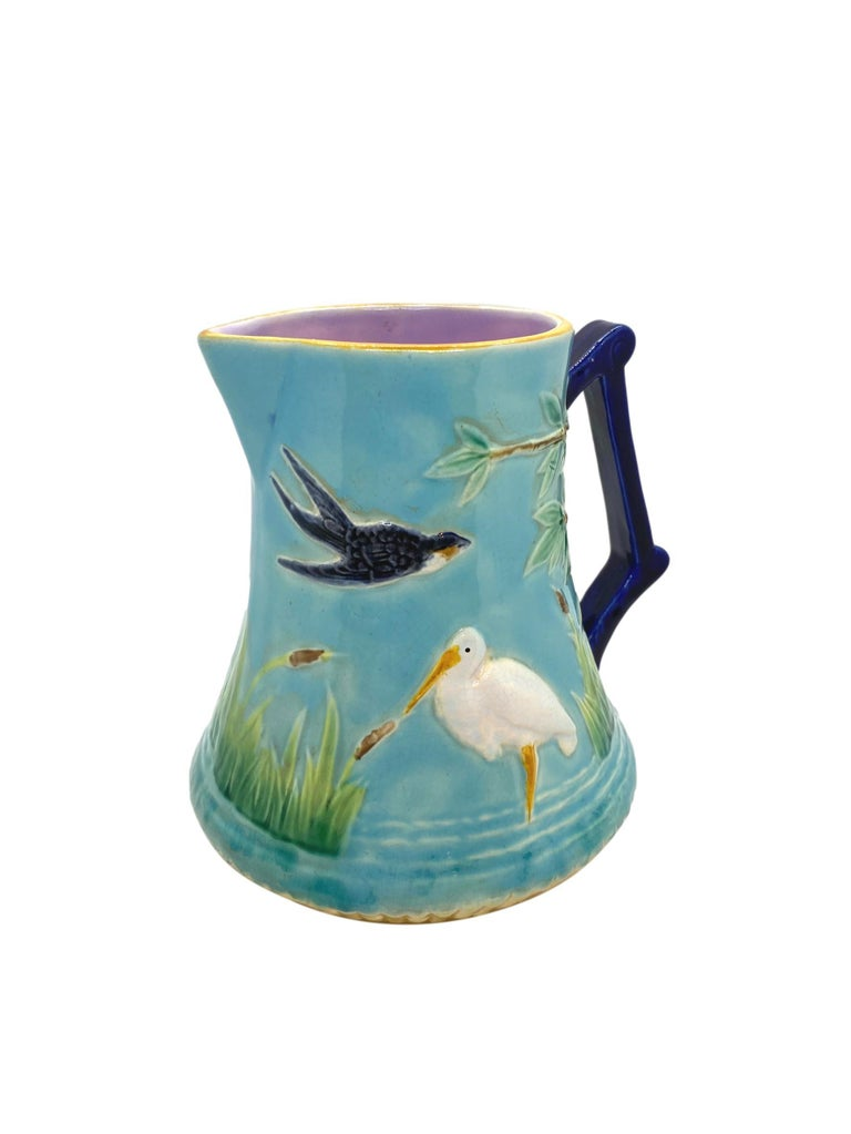 George Jones Majolica Stork in Marsh Pitcher, English, ca. 1878, the relief molded body of tapering cylindrical form, with storks in simulated water among bullrushes and birds to either side, with a tree and branches issuing from under the cobalt
