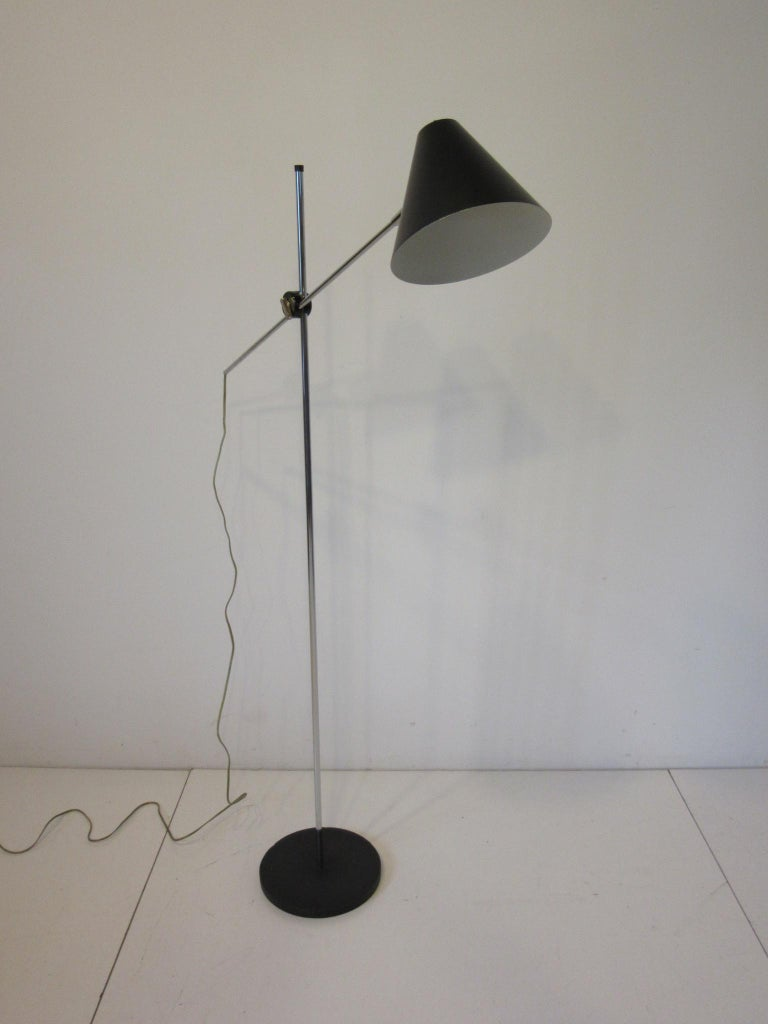 A chrome and satin black cone lamp with adjustable shade height and tilting designed and manufactured by the George Kovacs Lighting company.