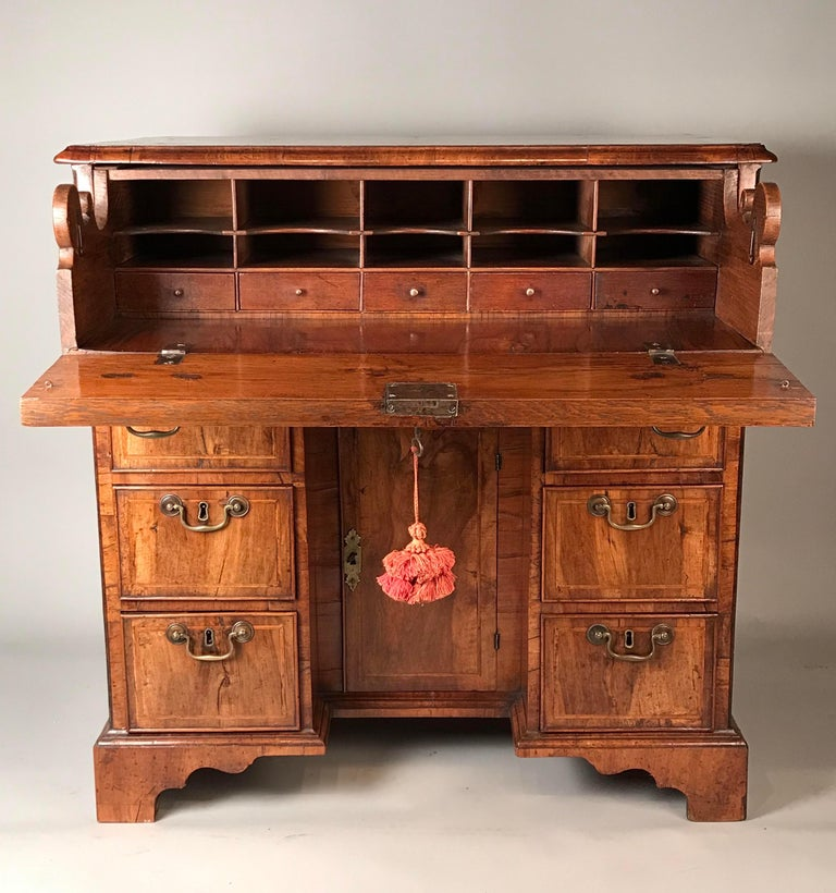 An early 18th century English walnut secrétaire kneehole desk. George I period (1714-1727). Ca 1720. Of exceptional lovely waxed honey color and old patina with well-matched veneers.  With a quarter-veneered top. Six short drawers below a hinged