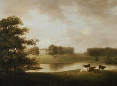 A view of an English Country House in idyllic parkland with cattle grazing