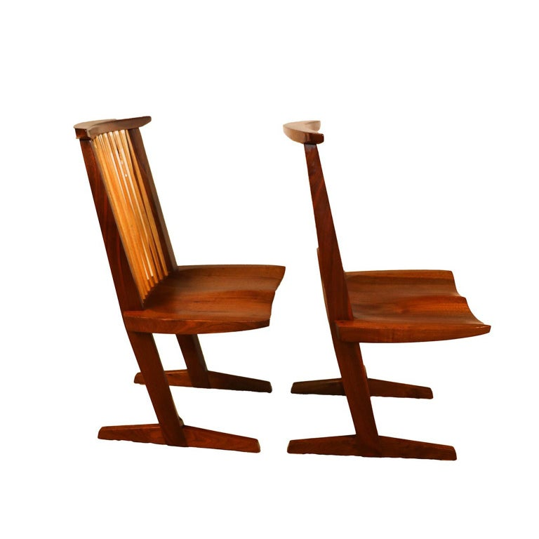 Designed by George Nakashima in 1985. This gorgeous pair of clean and solid sculptural teak chairs have been well cared for over the years, in nearly brand new original condition. Features walnut and hickory spindled backs, flat curved crest rails,