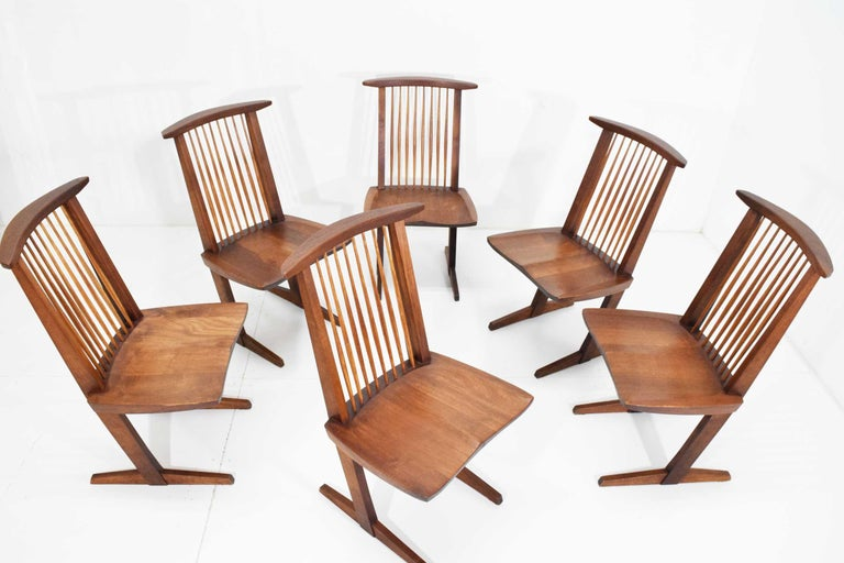 George Nakashima Conoid dining chairs in black walnut and hickory. New Hope, Pennsylvania, 1970s. Four signed with client's name