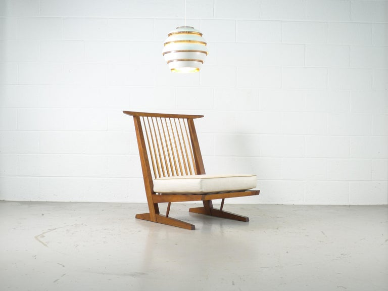 George Nakashima studio, a Conoid lounge chair in American black walnut with Hickory spindles.  Looks to have the original cushions, in stunning vintage condition.  Provenance available.