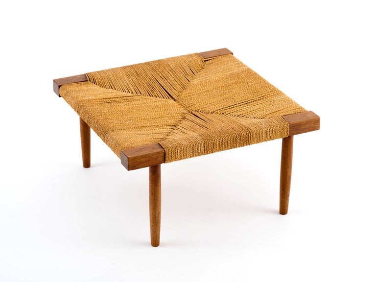 A low stool or ottoman in walnut with grass rope seat by George Nakashima, circa 1965. This design is both scarcer and larger than the more commonly-seen 12.5 inch height stool with splayed legs and it's in remarkable condition, particularly the