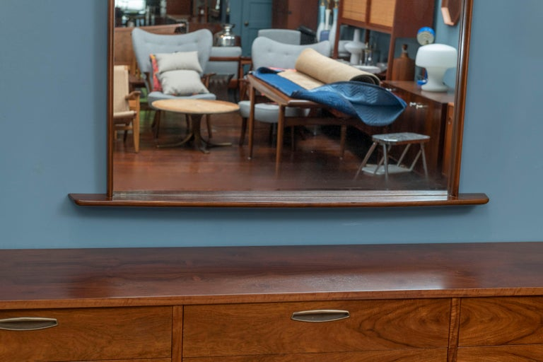 George Nakashima origins mirror. Stunning, substantial wall mirror constructed of solid walnut. Sculpted beams elegantly extend beyond the mirror's frame. Has been lovingly used, and in excellent vintage condition. Wood is gleaming, and mirror has