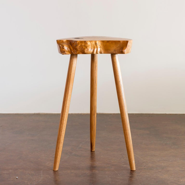 Petite, exceptionally proportioned early side table in ash featuring a triangular top with live edges and tapered legs.