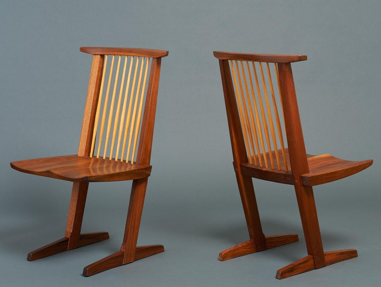 George Nakashima (1905–1990)   An exceptional pair of Conoid chairs by Pennsylvania studio craft movement patriarch George Nakashima, among the last he sculpted before his death. In carved black walnut shot through with a tactile red and blond