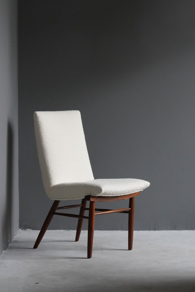 A side chair, designed by George Nakashima, produced by Widdicomb Furniture Company, Grand Rapids, Michigan, America, 1960s.  Features finely turned walnut, overstuffed seat reupholstered in Knoll Bouclé fabric.