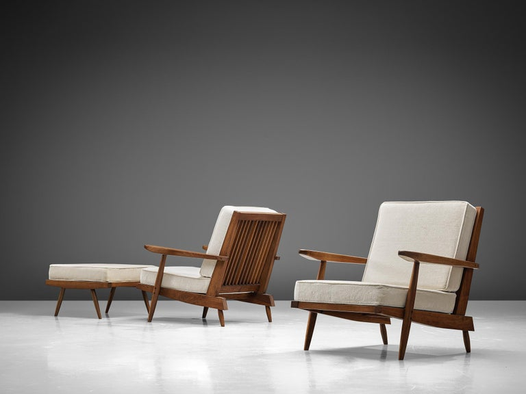 George Nakashima, armchairs, walnut, ivory fabric, United States, design, circa 1950.   These quintessential spindleback armchairs and ottomans are designed by Nakashima. The chairs feature spindles at the back, referring with this detail to the