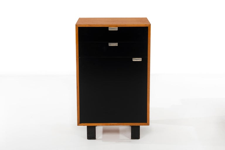 Classic Mid-Century Modern Design, George Nelson for Herman Miller storage cabinet, Primavera wood with black lacquer doors and silver plated J-pulls. 2 drawers with door concealing shelf.