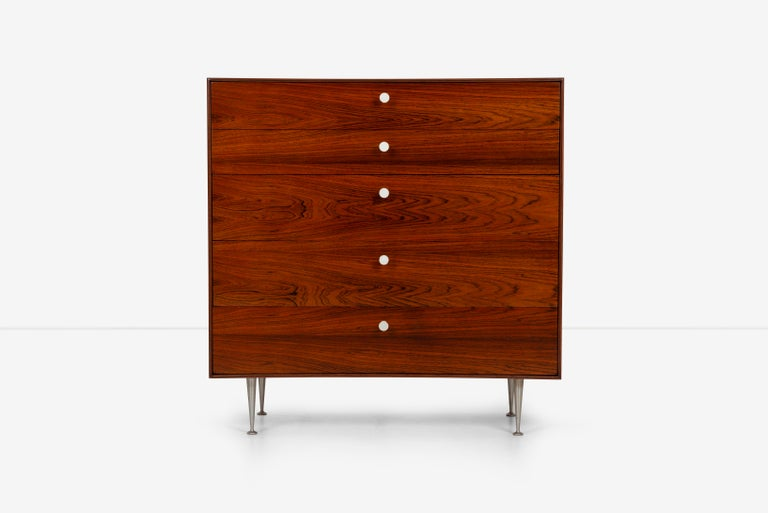 George Nelsonfive drawer thin edge rosewood dresser, dynamic rich rosewood graining, features five drawers with porcelain pulls and aluminum tapered legs.  Foil label inside drawer (George Nelson for Herman Miller).