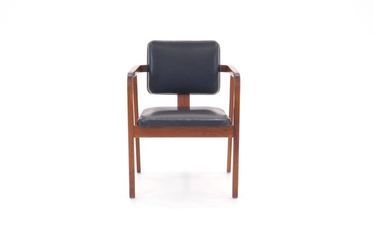 All original George Nelson armchair. Walnut frame, vinyl upholstery. Signed with the round Herman Miller medallion.