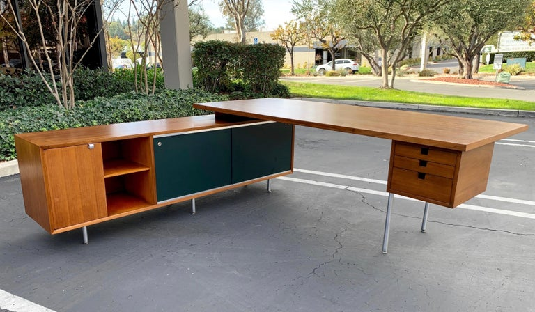 Mid-Century Modern, executive desk with credenza return by George Nelson for Herman Miller features a walnut desk with steel H legs that measures 84 x 36 x 30 with attached walnut office credenza with dark green almost black Masonite sliding doors