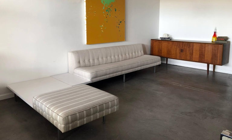 A stunning, iconic piece of Mid-Century Modern design, a George Nelson for Herman Miller sectional sofa! The sofa is in good vintage condition with neutral fabric and attached side tables with white laminate tops.