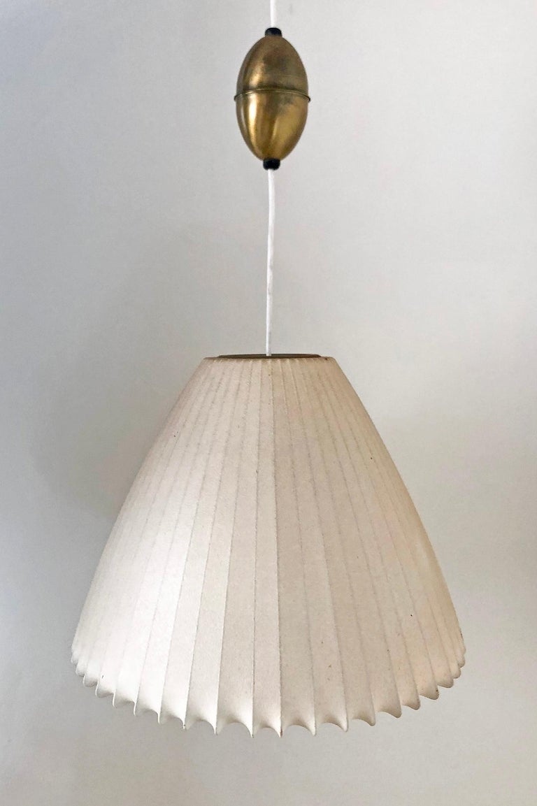 Designed in the 1950s this is one of the rarer George Nelson bubble lamp forms, the bell. This bell shaped pendant still retains its original Howard Miller labels, original patinated skin, and original brass components.  Pendant has original brass