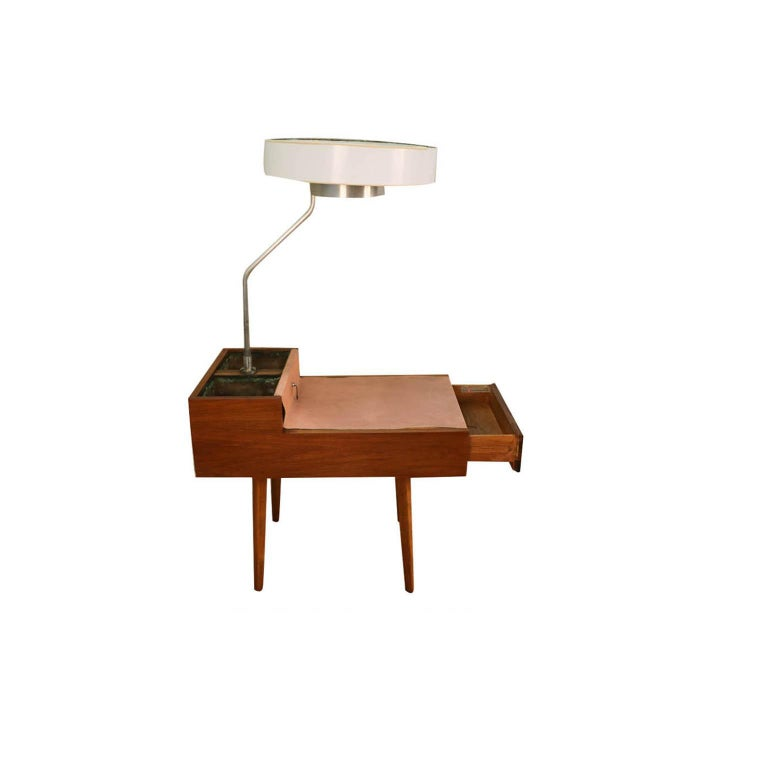Unique and rare Mid-Century Modern Model 4634-L side table with lamp and planters designed by George Nelson for Herman Miller, circa 1940s. Featuring a handsome walnut case with a coordinating and complimenting leather tabletop. A lamp rises from