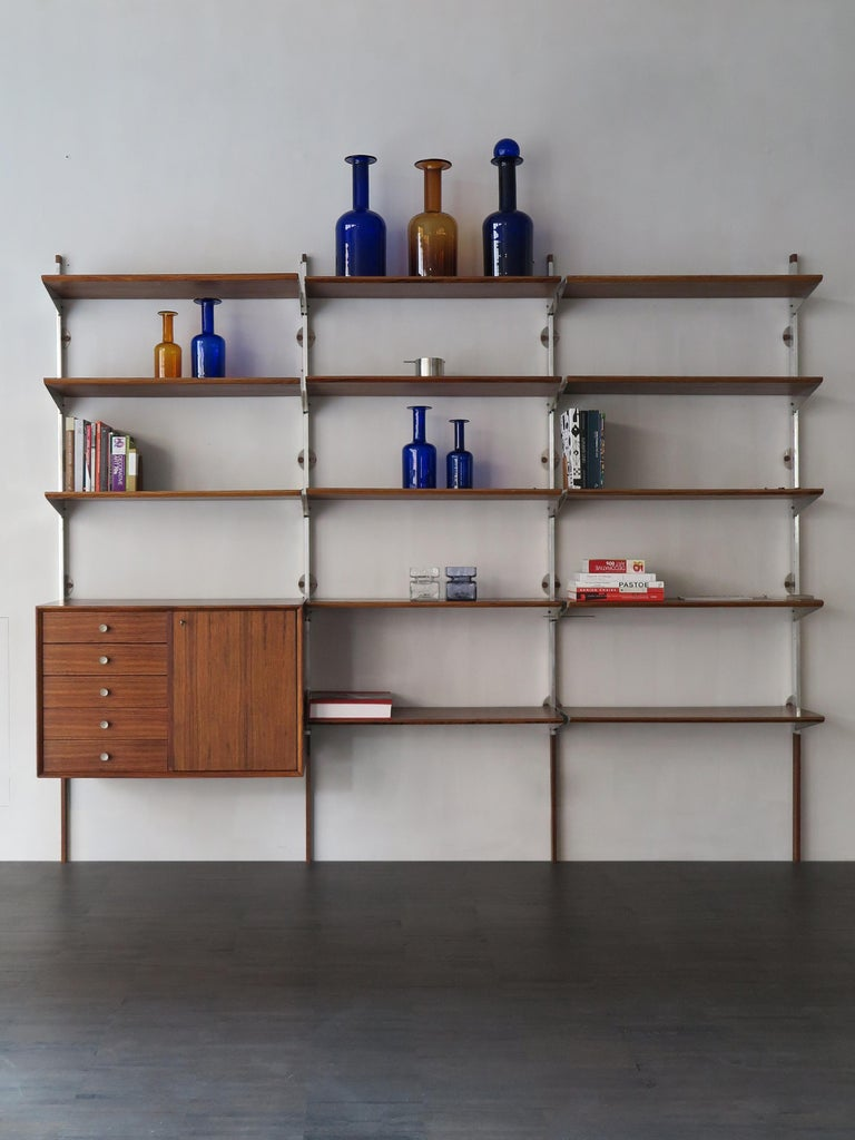 Dark wood wall system designed by George Nelson for Herman Miller with movable shelves, aluminum detail, circa 1950s.
