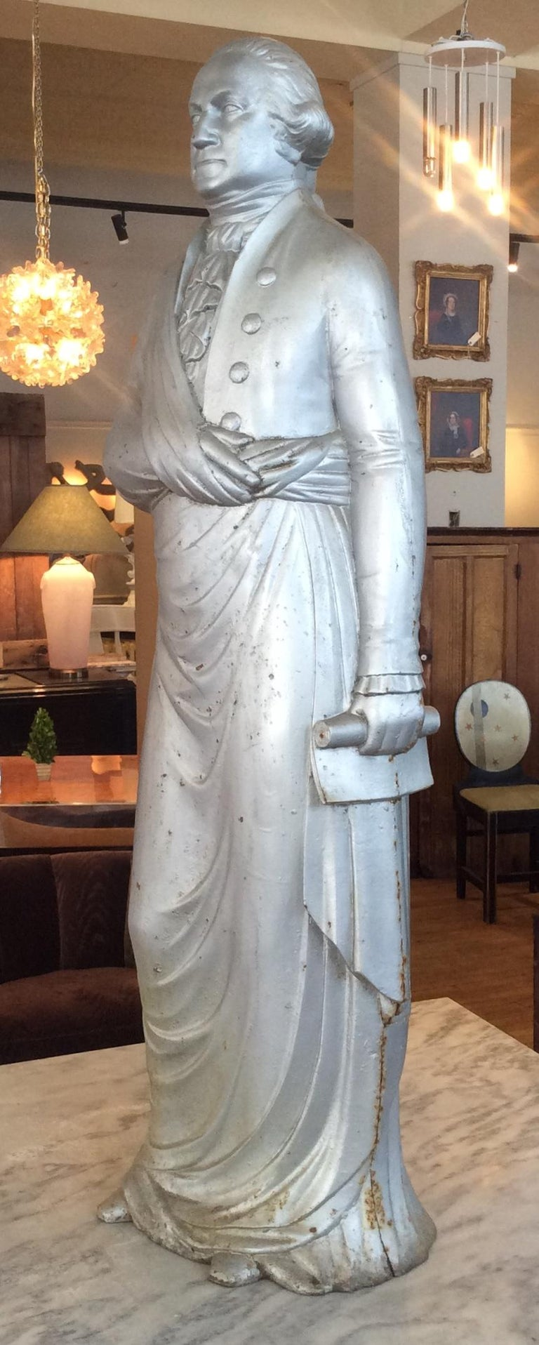 A rare example of this 19th century cast iron George Washington stove figure. The standing draped form holding a scrolled document in his left hand. These originally sat atop a 'dumb stove' and were designed to radiate heat into the room. (A dumb