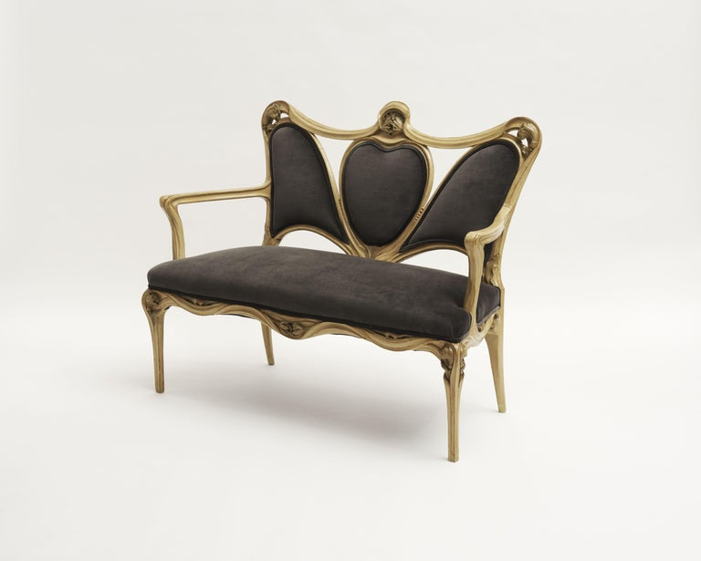 This settee is typical of De Feure's style at the turn of the 20th century. The high back with swooping lines, paired with straight legs curving toward their meeting with the seat, is reminiscent of pieces De Feure created for the, 1900 Paris
