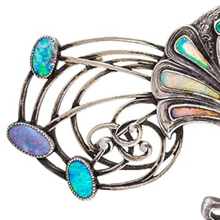 A French Art Nouveau silver cloak clasp with opals by Georges Fouquet. The cape clasp is decorated with 14 bezel set crystal opal plaques.  The clasp is designed as two intertwined peacocks with extravagant whiplash 'feathers'. Circa 1900.  Inspired