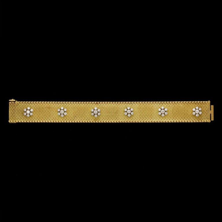 A beautiful gold and diamond bracelet by Georges Lenfant c.1965, designed as a straight strap of matte textured 18ct yellow gold edged with polished gold 'stiches' and applied along the centre with six ruby and round brilliant cut diamond flowerhead