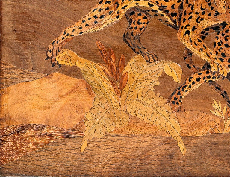 An exceptional marquetry panel by Georges Lucien Guyot, derived from his explorations and observations in the wilds of Africa. This rare marquetry panel depicts two Cheetahs fighting in a verdant landscape, picked out in exotic timbers including