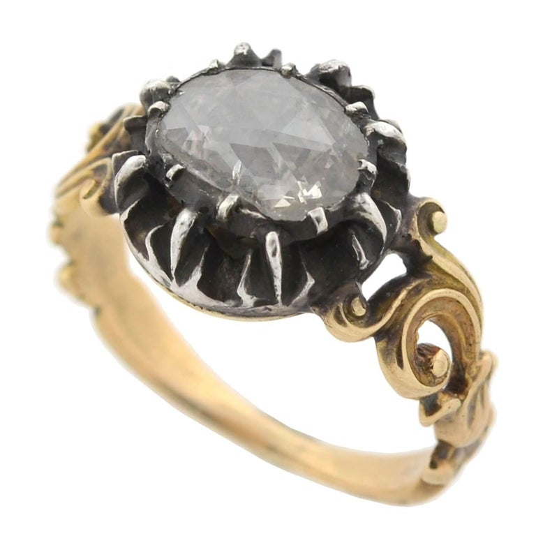 An exquisite old Rose Cut diamond ring from the Georgian era (ca1790)! This wonderful piece is crafted in 15kt yellow gold with a darkened sterling silver setting. A large, sparkling old Rose Cut diamond rests at the center, held within a closed