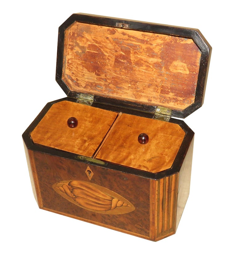 A delightful George III period, late 18th century Burr yew wood octagonal shaped tea caddy Having charming inlaid decoration, including Conch shells, and hinged lid enclosing lidded Divisions with fully working lock and key  (This is a very