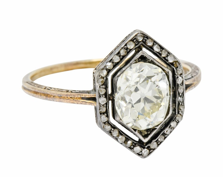 Centering an old mine cut diamond weighing approximately 1.70 carat, P color and VS clarity  Surrounded by halo of rose cut diamonds weighing approximately 0.30 carat total  Set in a tapered hexagonal mounting with a deeply ridged shank   Accented