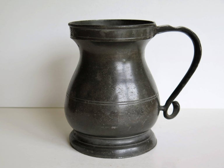 This is a good mid-18th century pewter tankard or mug with a baluster shape, fully stamped with GR and other markings.  This tankard has a lovely baluster pear shaped body on a flared skirt base and fairly deep top rim. The body has a double scribed